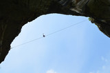Silhouette of vertical cliffs, young highline walker on a tightrope high in the blue sky