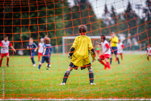 Young soccer goalie defending the net in the rain Poster