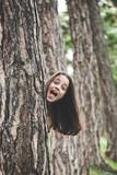 happy girl behind tree