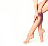 Fototapety Beautiful well-groomed female legs . Foot care . Epilation and depilation of hair on the feet . Smooth long slender bare foot .