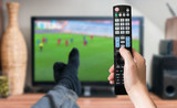 Man is relaxing with legs on table and is watching football match on tv with remote controller.