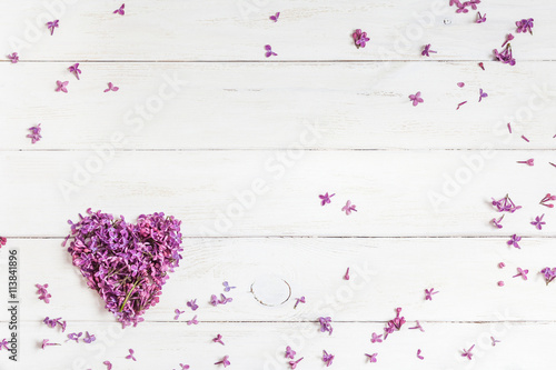 lilac flowers in the shape of heart on white wooden background, top view, flat lay