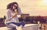 Красивая молодая брюнетка с кудрявыми волосами в солнцезащитных очках в жаркий летний день на улице города