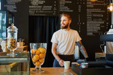 Fototapety Happy barista, small business owner standing behing the counter