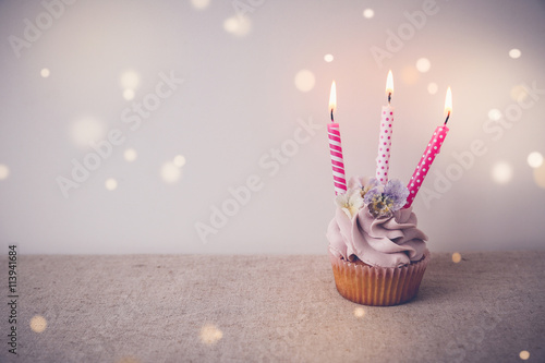 Poster Pink and purple Birthday cupcake with three candles, fairy light toning backgrou