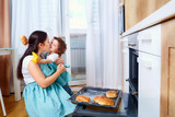 Mom and baby daughter in kitchen hugging and smiling. Mom teache