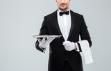 Waiter in tuxedo holding metal empty tray and napkin