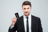 Handsome young businessman holding credit card