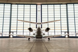 Private corporate jet parked in a hangar - 113968827
