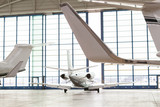 Small Passenger Airplane Leaving Bright Hangar - 113968875