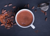 Cocoa in a cup and cocoa beans on the black background