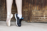 Feet dressed in dance pointe shoes and sports shoes