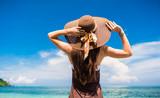 Frau im Sommer Urlaub mit Strohhut und Strandkleid genießt den Ausblick am tropischem Strand oder Meer - 113989226