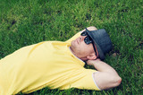man in a yellow T-shirt and hat lying on the grass