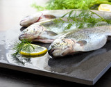 Rainbow trouts on a stone board with herbs and lemon