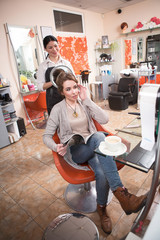 Beautiful lady reading magazine while having her hair dobe by hairdresser in hairdressing saloon. Closeup picture of cup of coffee.