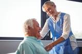 Nurse using stethoscope to take care of a senior man