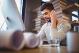 Businessman using cellphone at computer desk