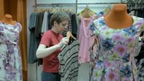 A clothing store with a variety number of merchandise to sell. A female customer looking for the right dress. Various sort of prints and fabrics are available. 4K UHD video footage.