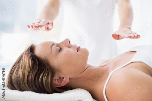 Midsection of therapist performing reiki treatment on woman