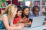 Happy multi ethnic classmates looking at laptop