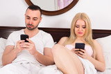 Couple with phones in bed.