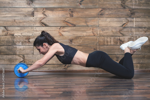 fototapeta na ścianę Attractive woman with slim stomach do abdominal exercises with wheel