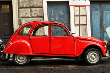 Red retro car on the street in Rome