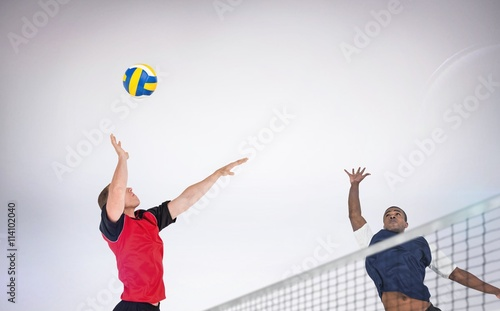 Fototapeta Composite image of sportsman posing while playing volleyball