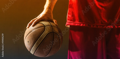 Close up on a basketball held by basketball player Poster