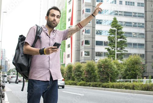 Fotobehang Tokio Young White Man With Cellphone Hailing Uber Taxi