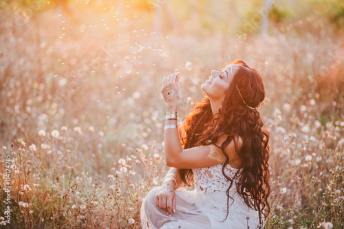 Poster Beautiful young woman with long curly hair dressed in boho style dress posing in a field with dandelions
