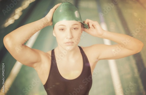 Pretty woman adjusting her bathing cap Poster
