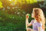 Little girl blowing soap bubbles, happy childhood concept.