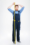 Happy funny young man measuring his body height using tape