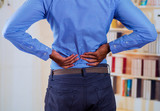 Man touching his back with his two hands, back pain