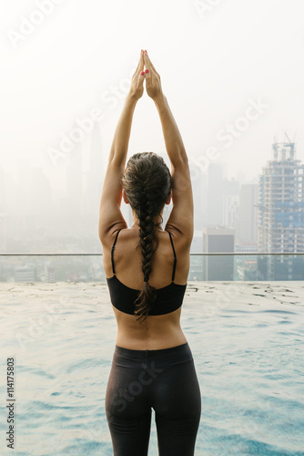 Obraz na plátne Relaxed young yoga woman in yoga pose near pool.