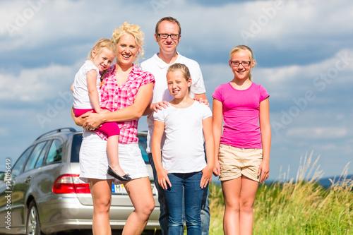 Poster Familie mit Eltern und Kinder stehen vor Auto