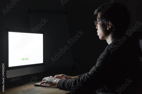 Man sitting and working with computer in dark office Poster