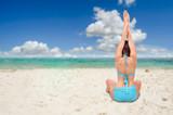 woman on tropical resort beach doing yoga relaxing