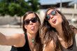 Two young women sticking out tongues while taking selfie