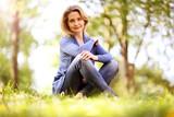 Frau im besten Alter sitzt in der Natur