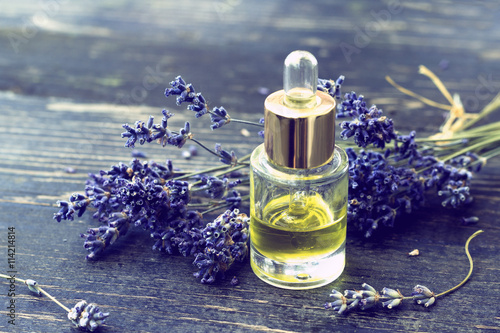 Plakat Bottle of lavender oil and lavender flowers on wooden background  - vintage styl