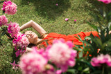 girl lying on the green grass under the pink peonies
