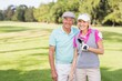 Smiling mature couple standing at golf course