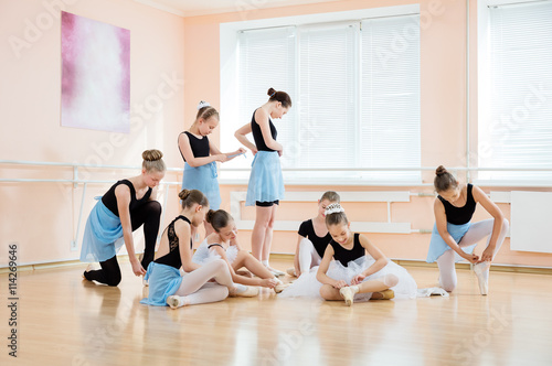 Young ballerinas putting on pointe shoes and adjusting costumes at ballet class © Andrey Bandurenko