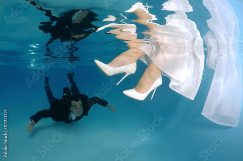 Poster Bride and groom, underwater wedding in a pool