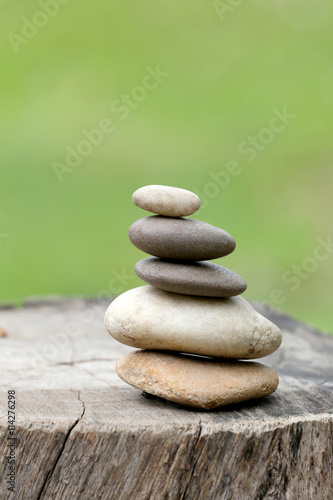 Balance Stones stacked to pyramid in the soft green background. Poster
