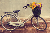 Photo of a bicycle with a basket full of field flowers