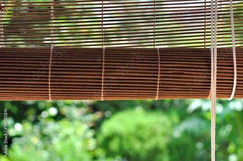 store bambou enroulé d'une fenêtre donnant sur jardin